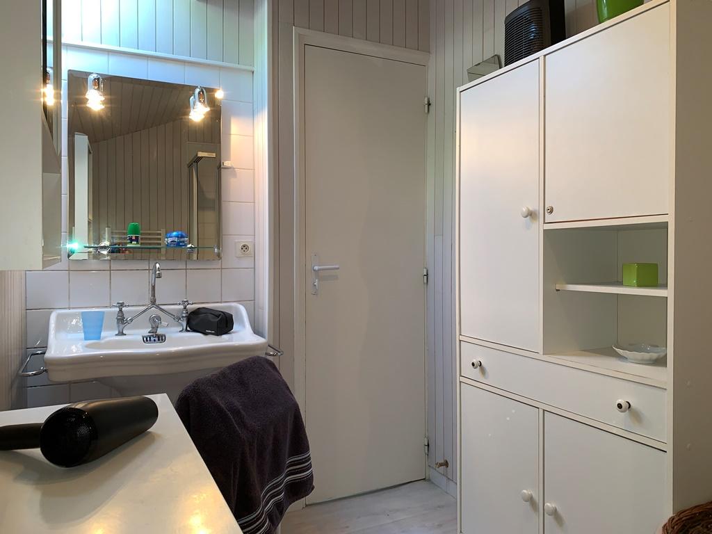 Salle de bain de la location meublé, lavabo et meuble de rangement